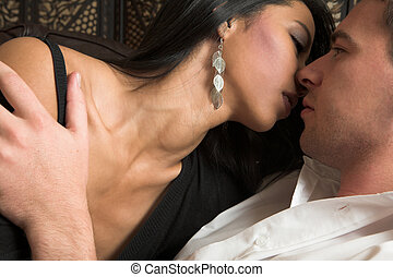 Intimate lovers embrace - Multi-ethnic couple in passionate...