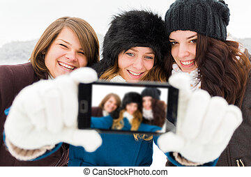 Girls Taking a Selfie - Laughing women taking photos with...