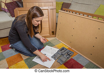 Girl reading instructions to assemble furniture -...