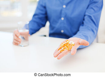 close up of male hand showing lot of pills - health,...