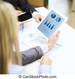business team with graph on tablet pc screen