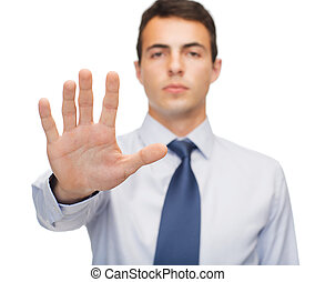 attractive buisnessman making stop gesture - business and...