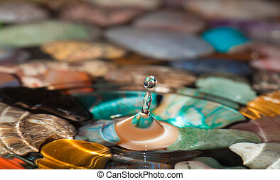 drops falling into shallow water, multicolored stones at the...