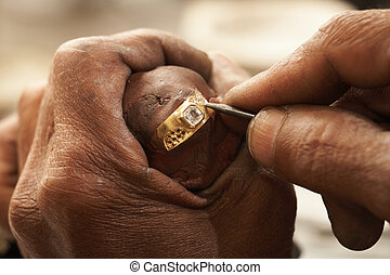 Goldsmith working on an unfinished 22 carat gold ring with...