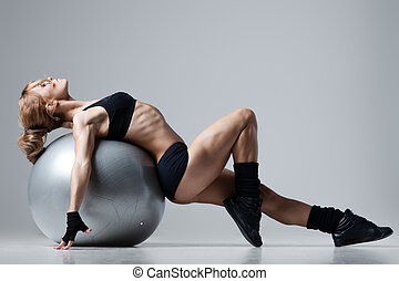 Fitness with gym ball - Athletic woman lies on a gym ball on...