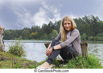 girl sitting on the shore of the lake.