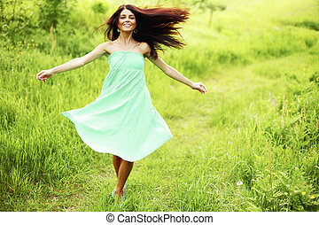 Woman running on meadow - Beautiful happy young woman...