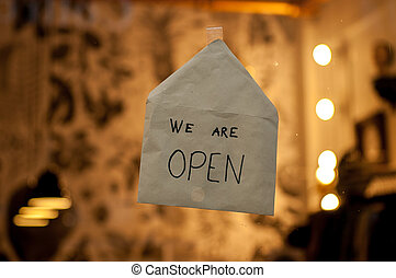 "White envelope on a shop window with the words ""we are open"" written on it"