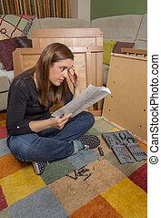 Girl reading instructions to assemble furniture - Surprised...
