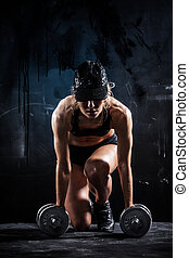 Sexy fitness - Sexy woman in a cap with dumbbells on dark...