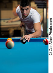 Man Playing Pool - Young Man Lining To Hit Ball On Pool...