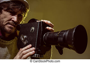 Man with old film movie camera. Shooting of the film,...