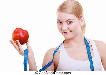 Sporty fit woman with measure tape fruit. Time for diet slimming.
