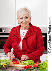 Smiled woman preparing meal - Happy elderly lady preparing...