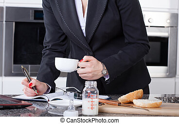 Multitasking woman in kitchen - W businesswoman drinking...