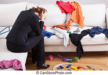 Unhappy woman in mess - An unhappy woman sitting on a sofa...