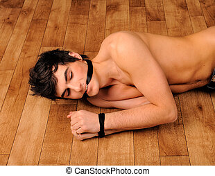 Man with nude torso binding by ribbon lying on a floor -...