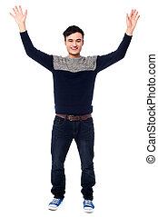 Cheerful young guy raising his arms