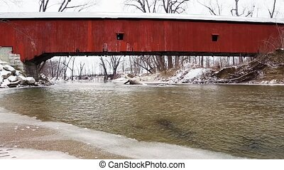 Wintry Covered Bridge Loop - Water flows through a snow...