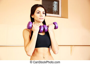 Young thoughtful fit woman doing exercises with dumbells at...