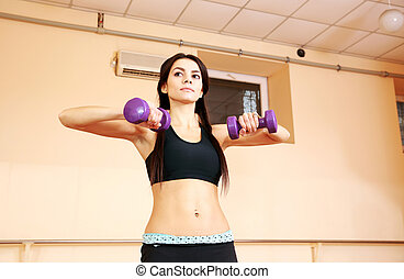 Young pensive fit woman doing exercises with dumbells at gym