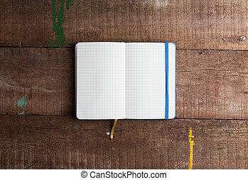 Open blank notepad with empty white pages laying on a wooden...