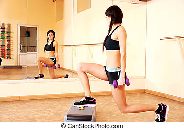 Young happy fit woman doing exercises with dumbells on step...
