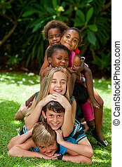 Diverse human pile - Multiracial children playing together...