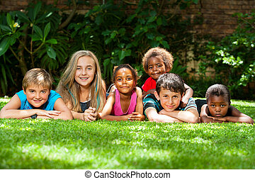 Diverse group of kids together in garden. - Diversity...