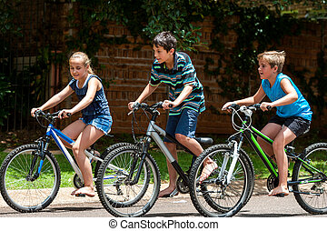 Kids riding theit bisycles - Motion shot of three...
