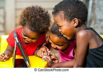 Threesome african kids having fun with tablet. - Close up...