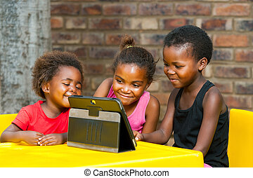 Three african kids playing together on tablet. - Portrait of...