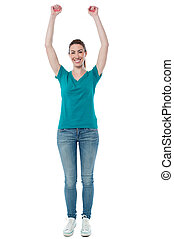 Excited woman raising her arms up - Full length image of...