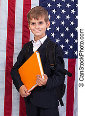 ?ute schoolboy is holding a book against USA flag - ?ute...