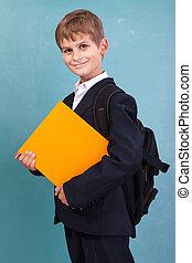 ?ute schoolboy is holding an orange book against school...