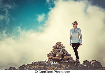 Woman Traveler on Mountain Summit with stones way sign and Clouds Sky on background Hiking Mountaineering Lifestyle summer