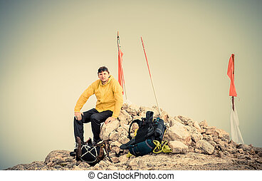 Man Traveler on Mountain summit with backpack Traveling Mountaineering concept fog on background