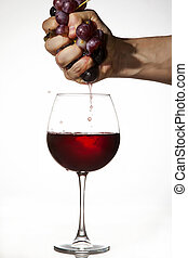Red Grapes squeezed by hand to make wine - Hand is squeezing...