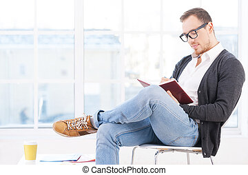 Handsome bookworm Thoughtful young man in shirt sitting on...