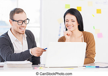 Working on the project together. Beautiful woman holding hand on chin and looking at the laptop while cheerful young man pointing on screen and smiling