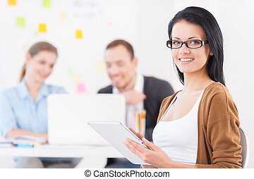 Happy to be a part of the team. Cheerful young woman holding digital tablet and smiling at camera while her colleagues working on the background