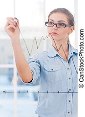 Attractive businesswoman drawing a graph. An attractive...