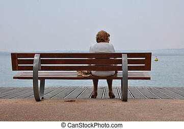 Old woman sitting on the bench by the lake