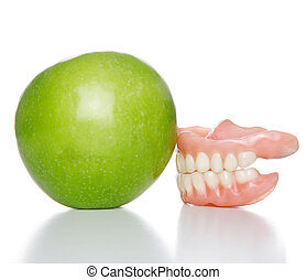 denture and apple - False teeth denture against green granny...