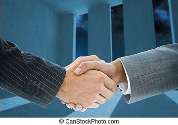 Composite image of business handshake against light shining...