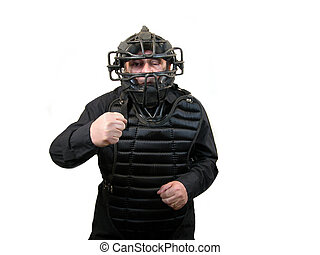 Strike - An Umpire in a mask and a chest protector calling a...