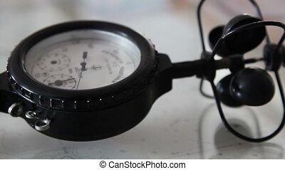 A black anemometer with a small wind vain on top of it an...