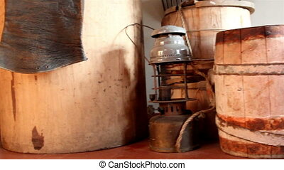 Three wooden barrels and an old lamp with chairs and ropes...
