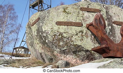 A rock with a rusty anchor - A rock with name tags and an...