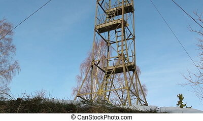 A steel tower on top of a hill under the blue sky